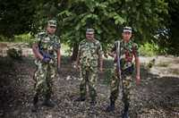 Three soldiers in military uniform carrying guns stand in front of a tree.
