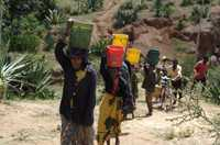 Women walking up hill carrying a bucket of water on their head.