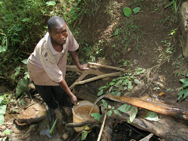 A boy collects water that flows from a spring, down a bamboo pipe and into his bucket. Sean Sprague, Caritas