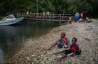 Children wait to board a small boat back to Walla Island after attending school on Malakula Island.