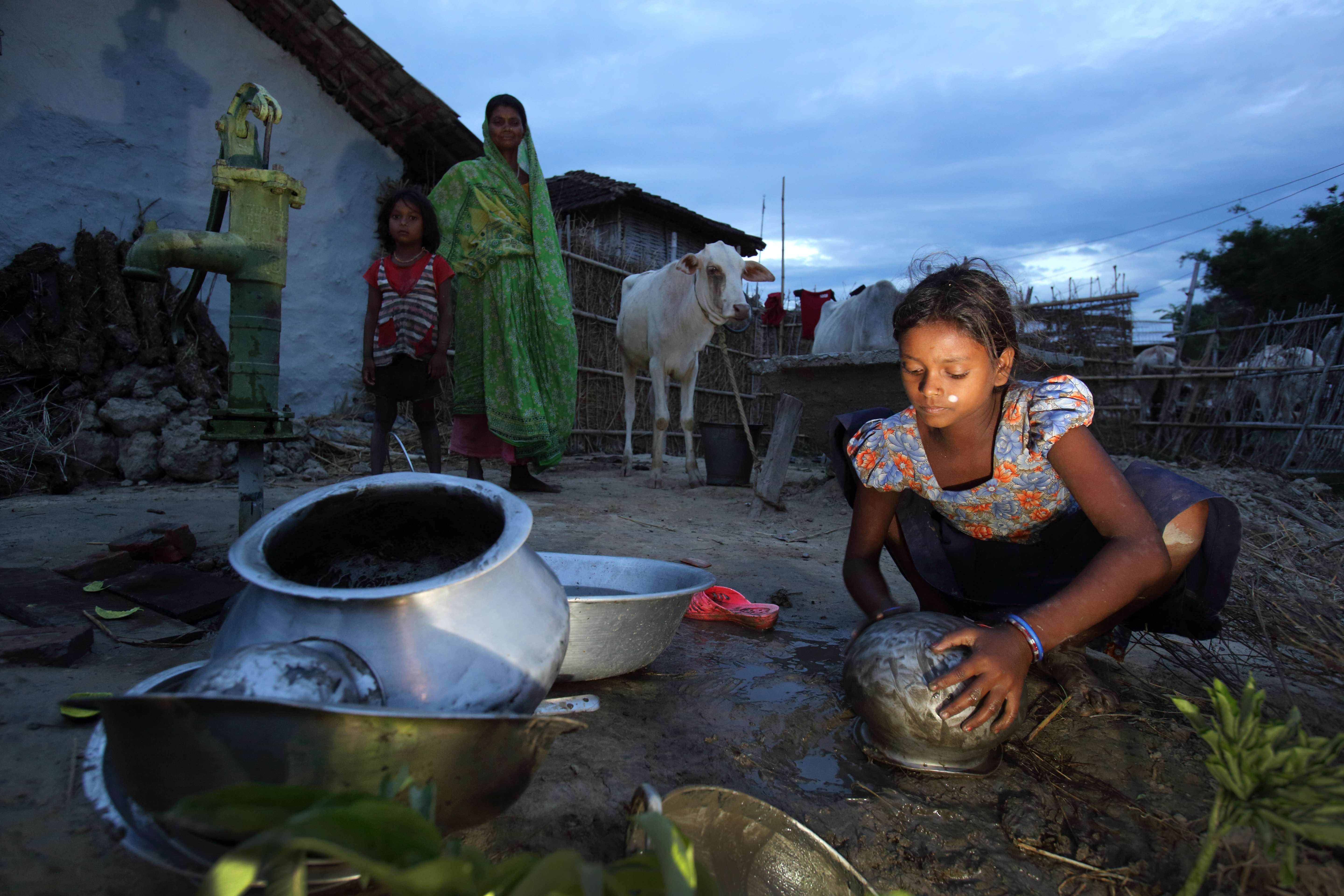 A young girl washes cooking utensils outside her home in Nepal. Photo by Jim Holmes for DFAT.