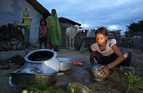 A young girl washes cooking utensils outside her home in Nepal.