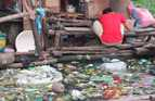 A young man works in front of his temporary house on the side of a river polluted with garbage.