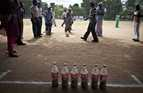Students line up to compete kicking a ball at six skittles made from drink bottles containing sand. .