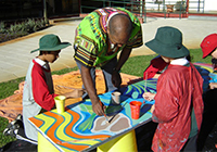 A man helps four children to paint a canvas.