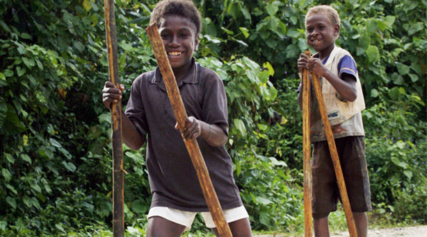 Boys enjoying walking on stilts in Solomon Islands. Photo by Rob Maccoll for AusAID