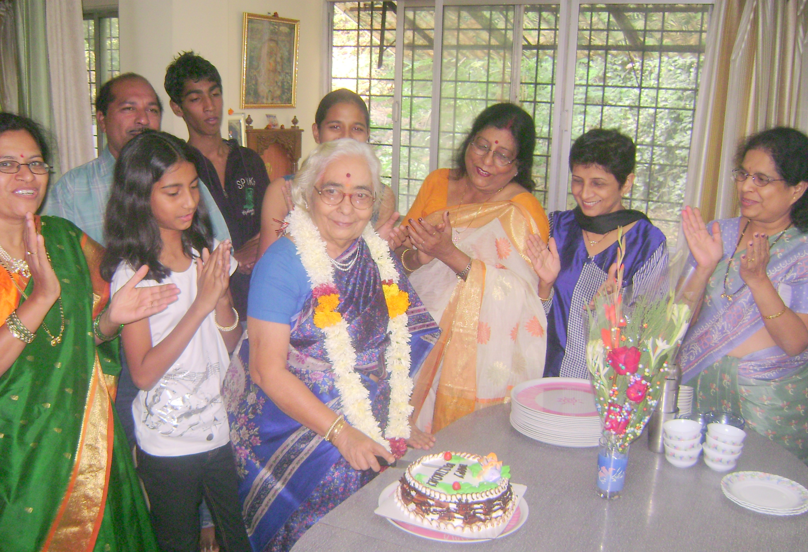 A family gets together to celebrate their grandmother's 80th birthday in Pune, India. Photo by You4youths. This image is from Wikimedia, and is in the public domain.