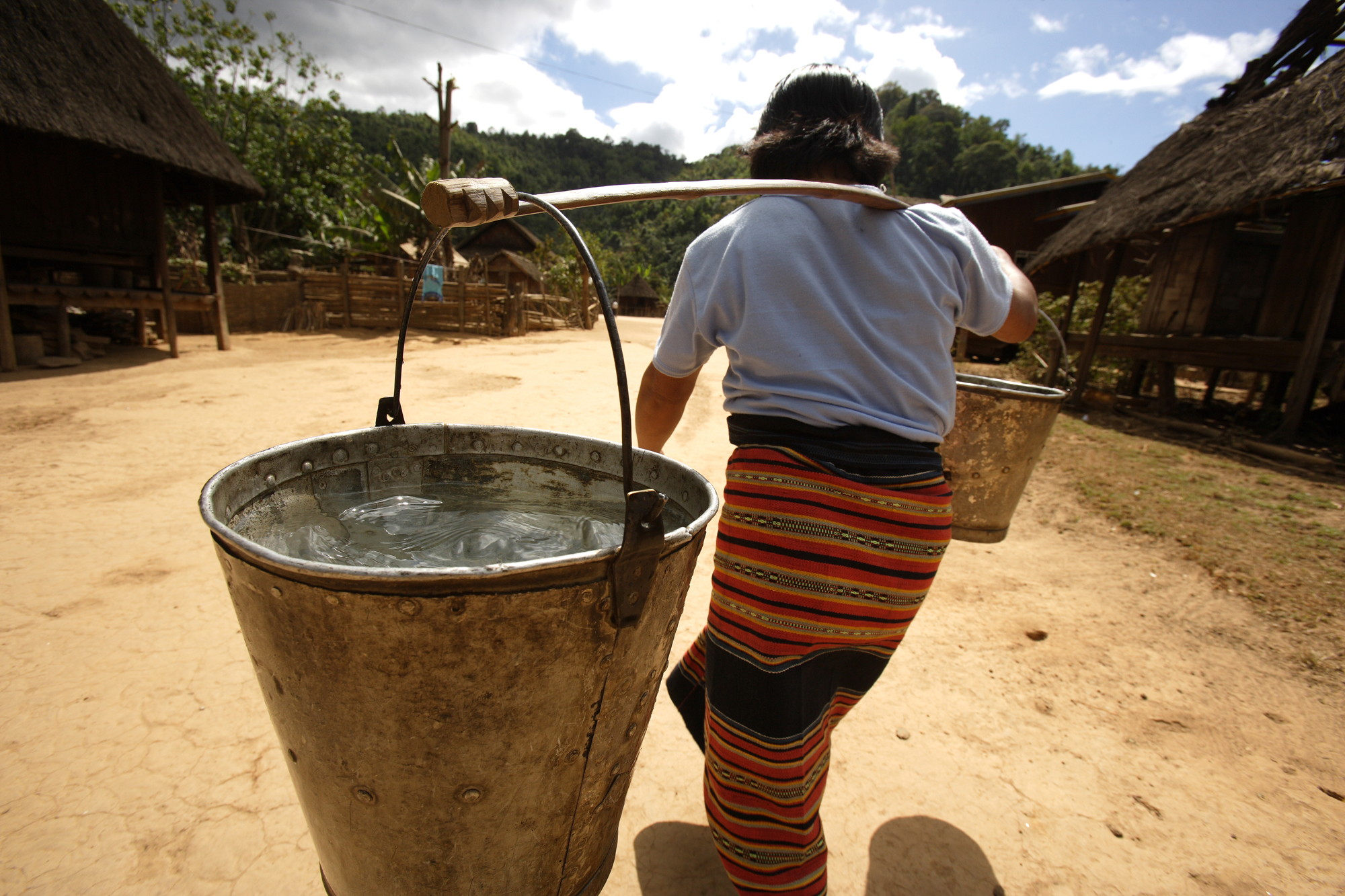A woman carries heavy buckets of water from a standpipe to her home near Sekong, Laos. Photo by Jim Holmes for AusAID