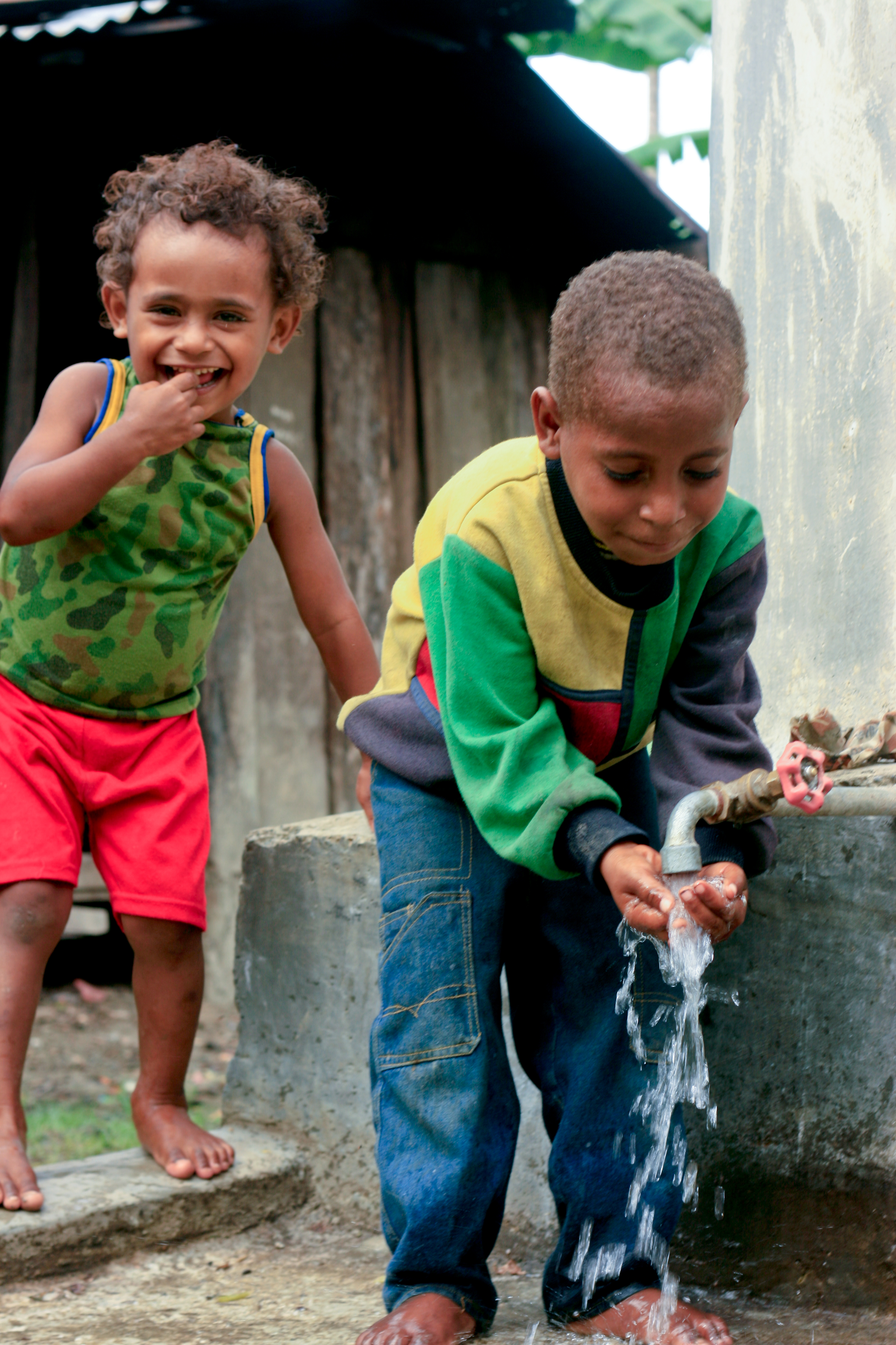In a crowded urban area of Jakarta, Indonesia, young boys use tank water to stay healthy and clean. Photo by AusAID