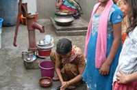A group of people use water from a pump for washing themselves and their dishes.