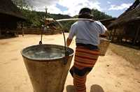 A woman carries heavy buckets of water from a standpipe to her home near Sekong, Laos.