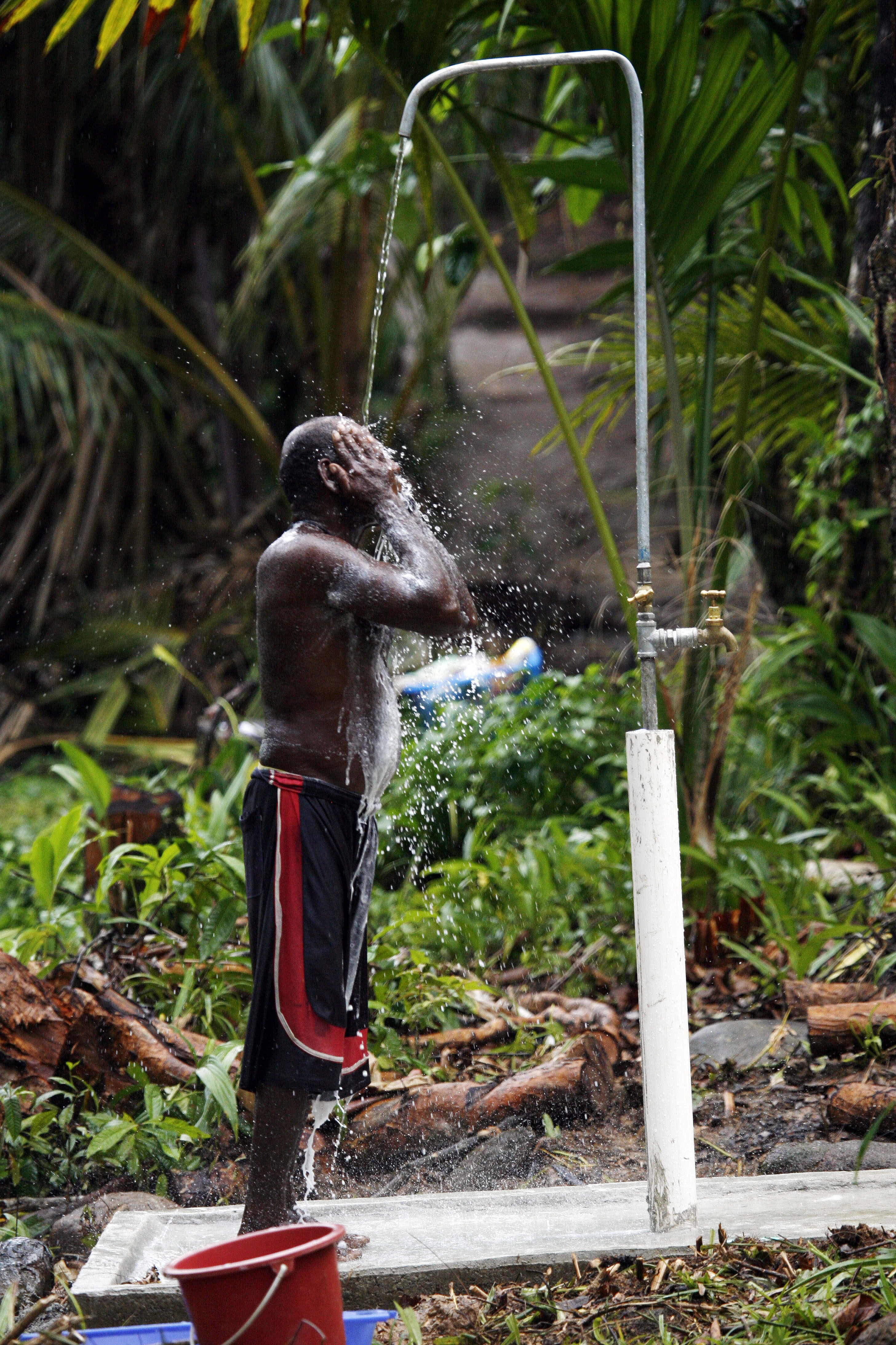 Peter Bua has a shower at a new water point in Nusa Barooka village, Solomon Islands. Photo by Rob Maccoll for AusAID