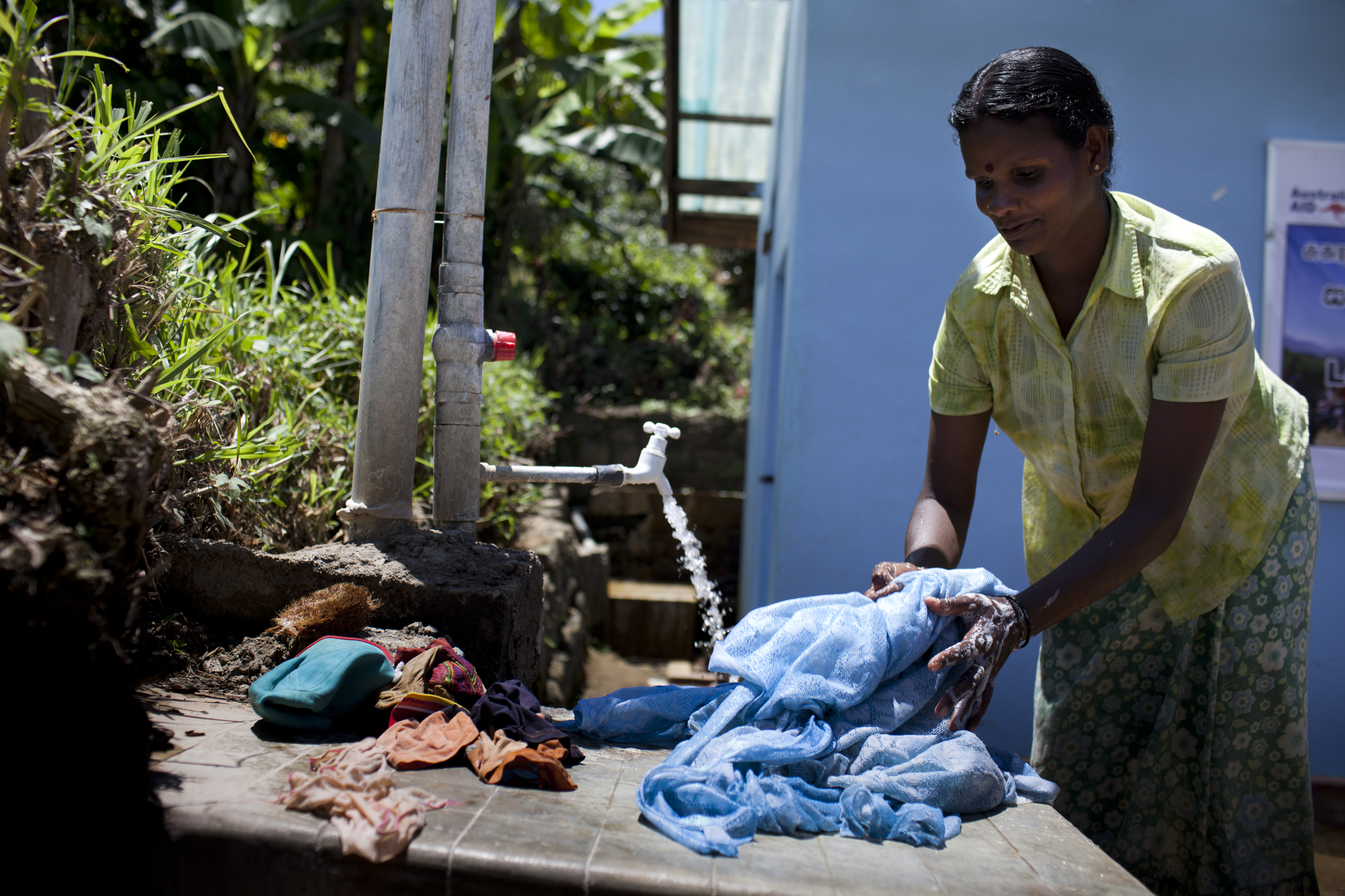 A woman uses a new village tap to wash clothes in Mactuff, Sri Lanka. Photo by Conor Ashleigh for DFAT