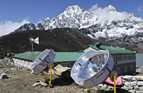 Two large circular solar cookers catch the sun outside a large building in snowy mountainous area.