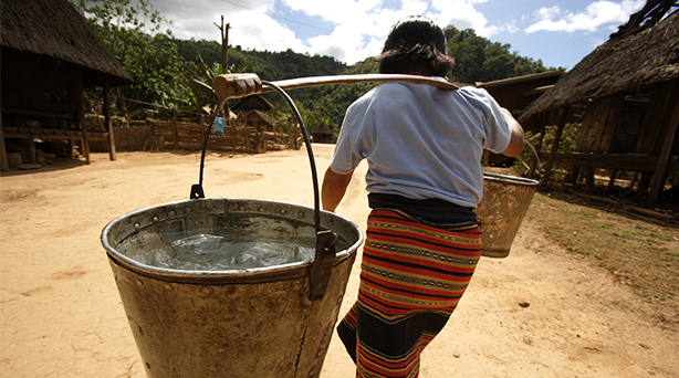 A woman carries heavy buckets of water for washing to her home in Sekong, Laos. Photo by Jim Holmes for AusAID